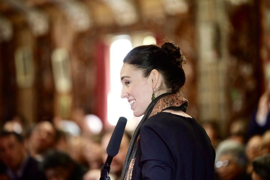 Jacinda Ardern smiling at a microphone