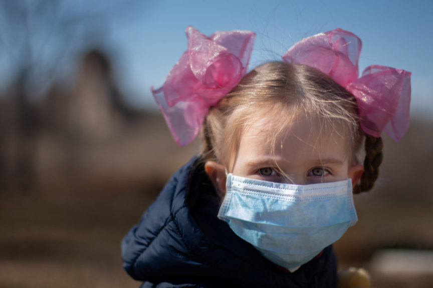 A child wearing a surgical mask