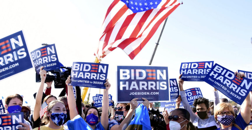 Crowds holding Biden-Harris placards celebrate the announcement of their victory in the US election