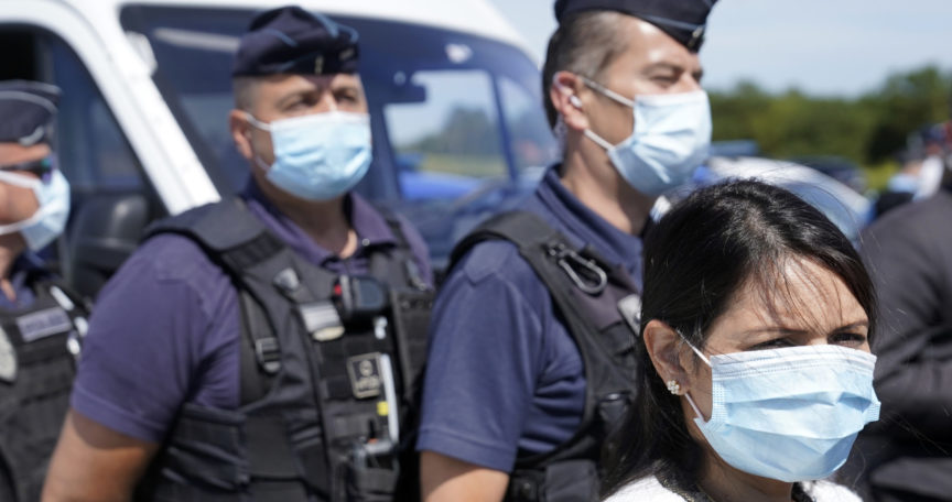 Priti Patel stands beside a number of French border guards in Calais, all wearing face masks.