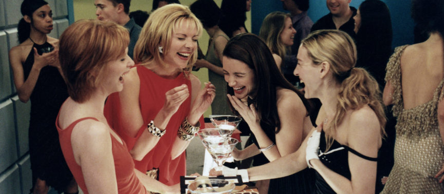The four protagonists of sex and the city stand in a cocktail bar laughing