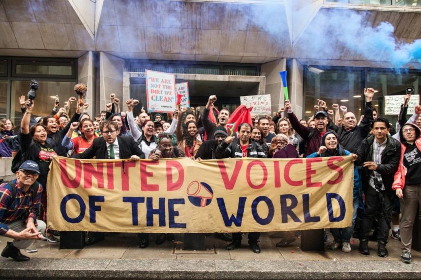 A group of workers stand with raised fists behind a banner that reads 'United Voices of the World'