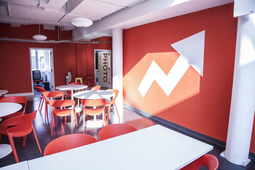 A picture of the offices of BuzzFeed, with white tables and red chairs, and a red wall with the company's distinctive white arrow