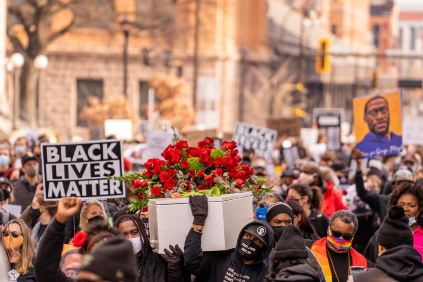 A crowd carries a white coffin covered with red roses. A placard nearby reads 'Black Lives Matter'
