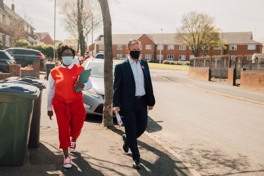 Labour leader Keir Starmer walks besides a local Labour campaigner on a street in Sandwell