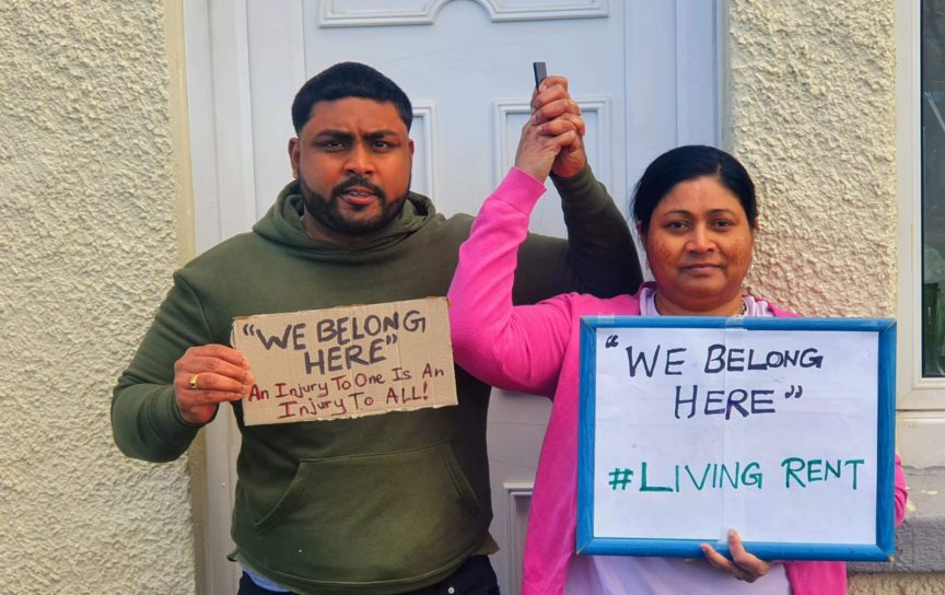A man and woman hold hands aloft as they hold signs with slogan 'We belong here'