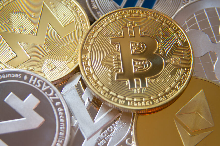 A pile of silver and gold coins embossed with the logos of various cryptocurrencies, including bitcoin.