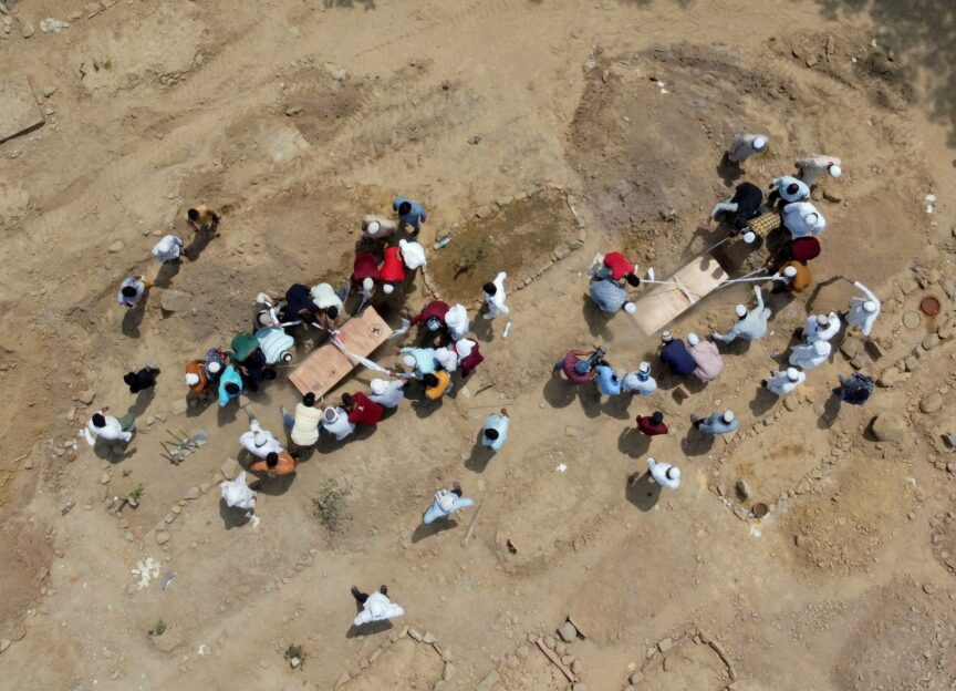 People bury the bodies of Covid-19 victims at a graveyard in New Delhi, India, April 2021. Ninian Reid/Flickr
