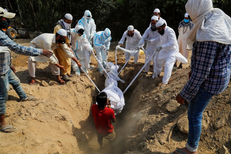 People lower the body of a man who died from Covid-19 into a grave during his funeral at a graveyard in New Delhi, April 2021. Ninian Reid/Flickr
