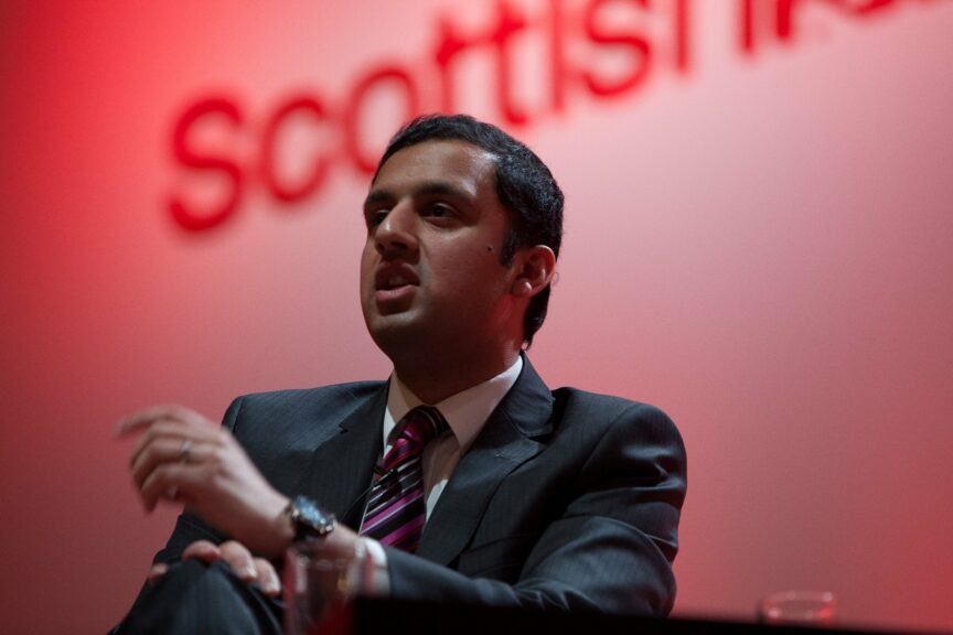 Scottish Labour leader Anas Sarwar sitting cross-legged in front of a sign that reads 'Scottish Labour'