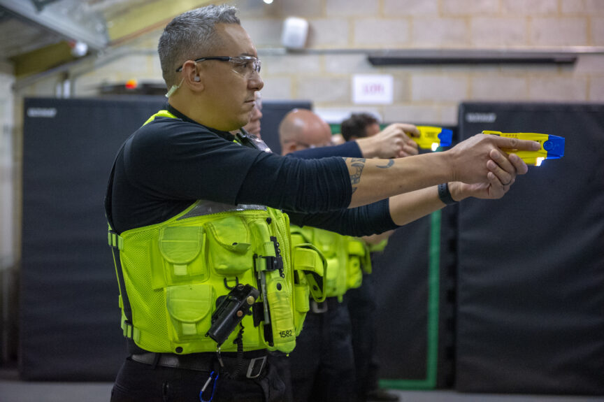 A British police officer wearing a blue shirt, yellow vest and protective goggles holds up a Taser at a shooting range.
