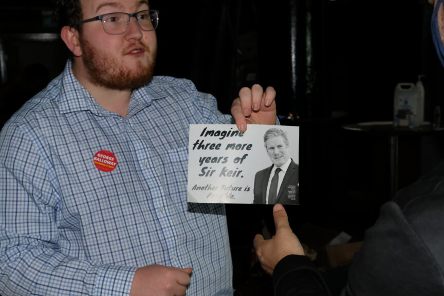 A campaigner holds a leaflet saying 'imagine three more years of sir Kier'